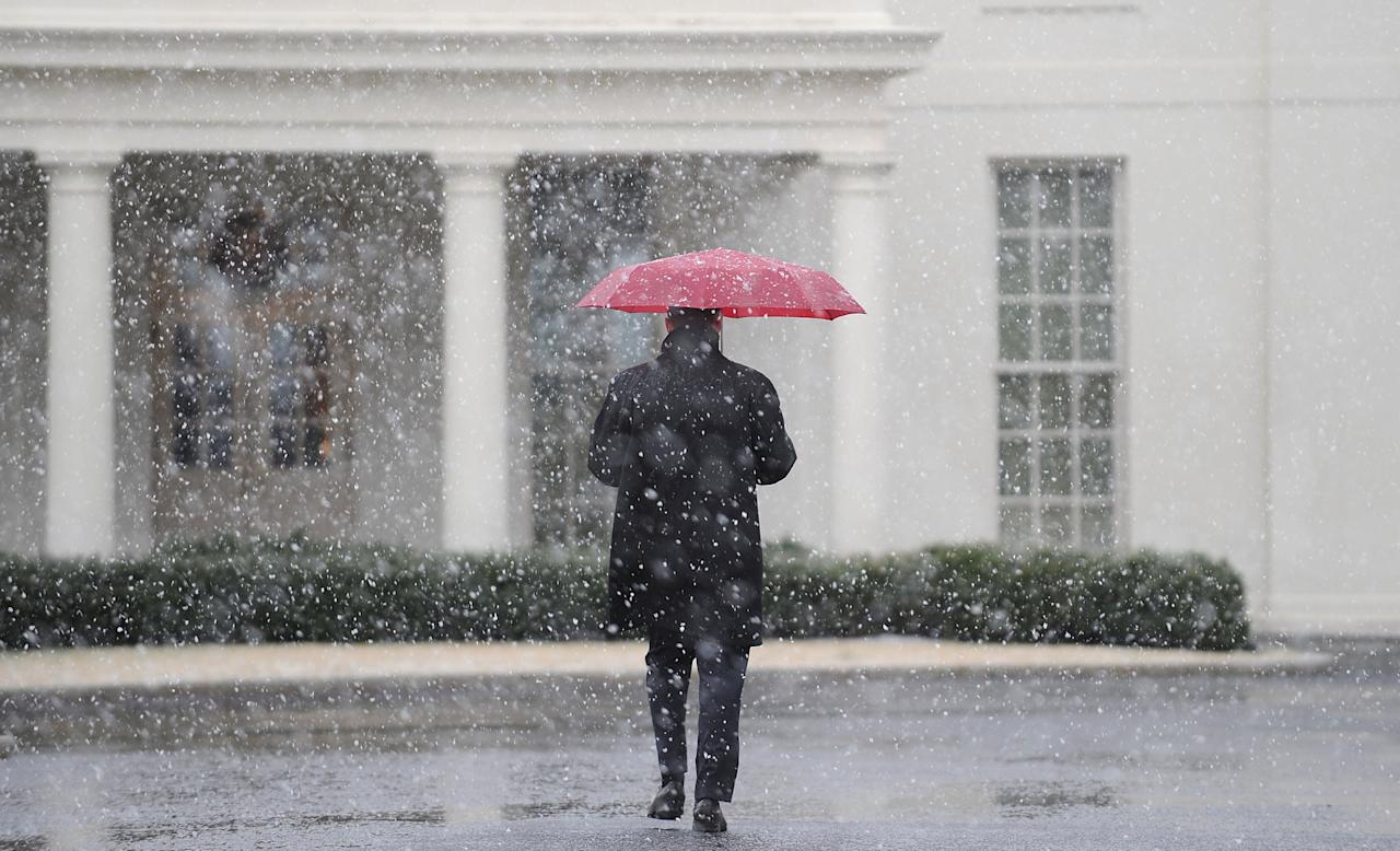 WASHINGTON, DC - MARCH 6:  (AFP OUT) A White House staffer walks to the West Wing during a snow storm at the White House March 6, 2013 in Washington, DC. The snow forced all major school systems in the area to close, including today's White House press briefing .  (Photo by Olivier Douliery-Pool/Getty Images)