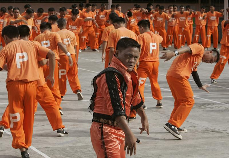 """FILE - In this June 27, 2009 file photo, inmates at the Cebu Provincial Detention and Rehabilitation Center on the island province of Cebu in central Philippines dance to the late Michael Jackson's """"We Are The World"""" to pay tribute to the music icon. The Filipino inmates whose choreographed """"Thriller"""" dance has attracted 52 million YouTube hits since 2007 are getting their own stories told in a movie. Director Marnie Manicad says the action drama """"Dance of the Steel Bars"""" was shot in the Cebu provincial prison, the same place where the inmates dressed in orange uniforms danced to global fame. Manicad co-directed the movie with Cesar Apolinario. It will be released in June, 2013. (AP Photo/Bullit Marquez, File)"""