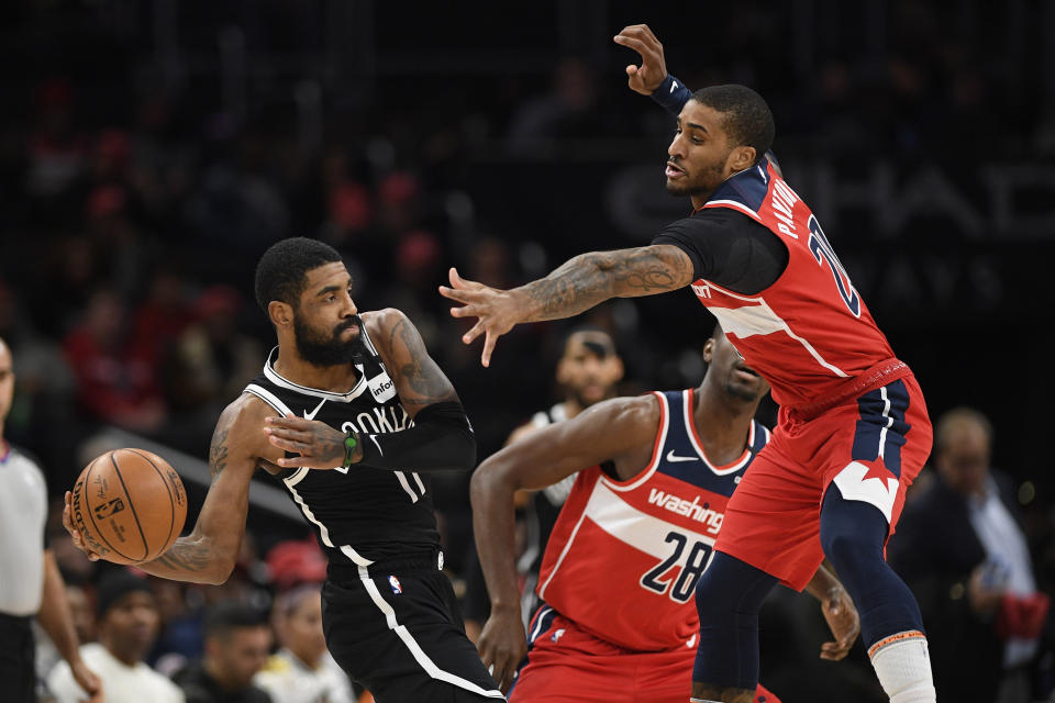 Brooklyn Nets guard Kyrie Irving (11) looks to pass as he is defended by Washington Wizards guard Gary Payton II (20) and center Ian Mahinmi (28) during the first half of an NBA basketball game, Saturday, Feb. 1, 2020, in Washington. (AP Photo/Nick Wass)
