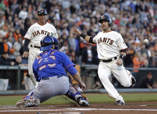 San Francisco Giants' Marco Scutaro, right, begins his slide into home plate before being tagged out by New York Mets catcher Anthony Recker during the first inning of a baseball game Tuesday, July 9, 2013, in San Francisco. Looking on is Giants third base coach Tim Flannery. Scutaro was trying to score from first after Pablo Sandoval doubled to left field. (AP Photo/Eric Risberg)