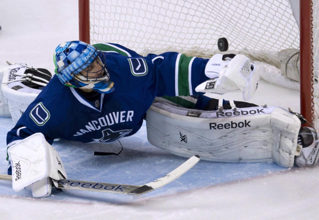 FILE - In this Nov. 17, 2013, file photo, a shot by Dallas Stars Erik Cole sails past Vancouver Canucks goalie Roberto Luongo during an NHL hockey game in Vancouver, British Columbia, Sunday, Nov. 17, 2013. The Canucks have traded Luongo to the Florida Panthers. (AP Photo/The Canadian Press, Jonathan Hayward)