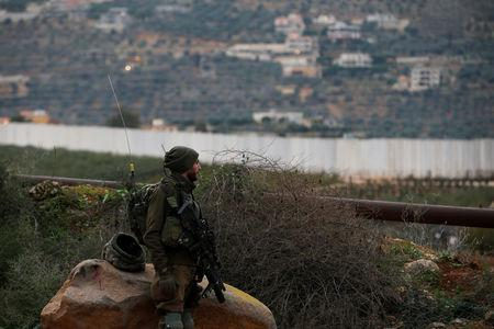 """FILE PHOTO: FILE PHOTO: An Israeli soldier guards near the border with Lebanon, the morning after the Israeli military said it had launched an operation to """"expose and thwart"""" cross-border attack tunnels from Lebanon, in Israel's northernmost town Metula December 5, 2018. REUTERS/Ronen Zvulun/File Photo/File Photo"""