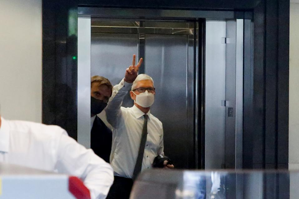 Apple CEO Tim Cook gestures from the elevator as he arrives to speak during a weeks-long antitrust trial at federal court in Oakland, California, U.S. May 21, 2021.  REUTERS/Brittany Hosea-Small
