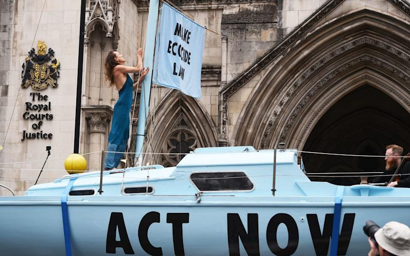 Protesters from Extinction Rebellion on a boat they have parked outside the Royal Courts of Justice in London - PA
