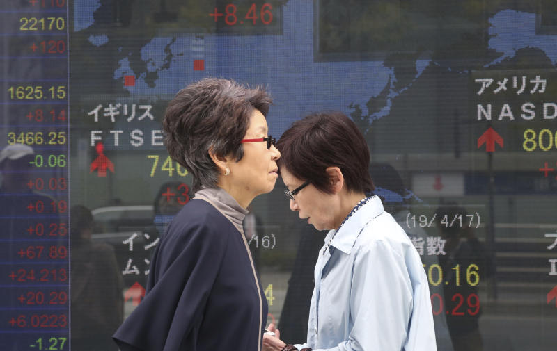 People walk by an electronic stock board of a securities firm in Tokyo, Wednesday, April 17, 2019. Shares were mixed in a narrow range Wednesday as China announced its economy grew at a 6.4 percent annual pace in the last quarter. (AP Photo/Koji Sasahara)