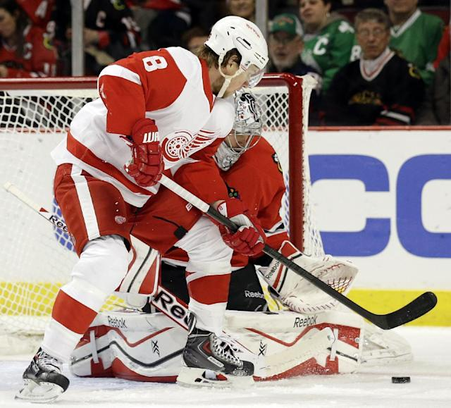 Detroit Red Wings' Justin Abdelkader (8) tries to shoot the puck against Chicago Blackhawks goalie Corey Crawford during the first period of an NHL hockey game in Chicago, Sunday, March 16, 2014. (AP Photo/Nam Y. Huh)