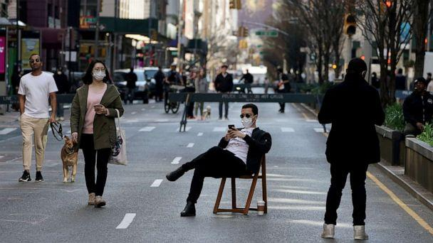 FILE PHOTO: A man sits on a chair as people walk on Park Avenue that was closed to vehicular traffic during the outbreak of coronavirus disease (COVID-19), in the Manhattan borough of New York City, New York, U.S., March 27, 2020. (Carlo Allegri/Reuters)