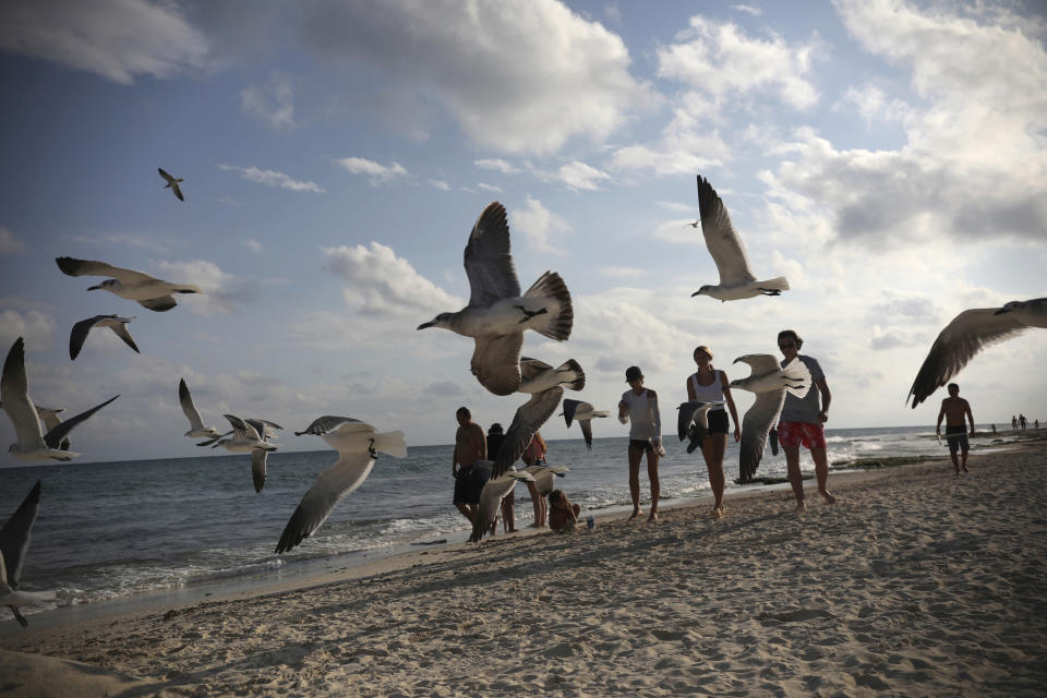 Tourists stroll on the shore of Xcalacoco beach in Playa del Carmen, Quintana Roo state, Mexico, Wednesday, Jan. 6, 202, amid the new coronavirus pandemic. Quintana Roo, the country's tourism crown jewel, home to Cancun, the Riviera Maya and Tulum, received more than 900,000 tourists spanning the end of 2020 and the start of 2021. (AP Photo/Emilio Espejel)