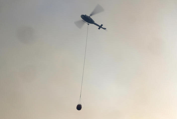A helicopter carries a water bucket to douse a fire near Bendalong, Australia, Friday, Jan. 3, 2020. Navy ships plucked hundreds of people from beaches and tens of thousands were urged to flee before hot, windy weather worsens Australia's devastating wildfires. (AP Photo/Rick Rycroft)