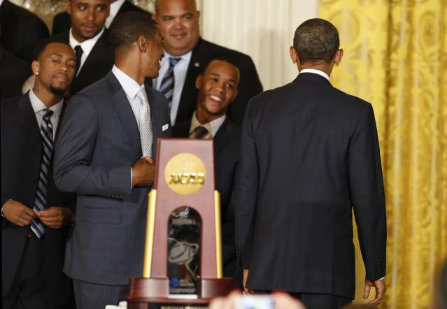 U.S. President Barack Obama (R) talks with UConn men's basketball player Ryan Boatright (L), coach Kevin Ollie (2nd L) and player Shabazz Napier (2nd R) at the end of a ceremony honoring the NCAA champion University of Connecticut Huskies men's and women's basketball teams in the East Room of the White House in Washington, June 9, 2014. REUTERS/Jim Bourg (UNITED STATES - Tags: POLITICS SPORT BASKETBALL)