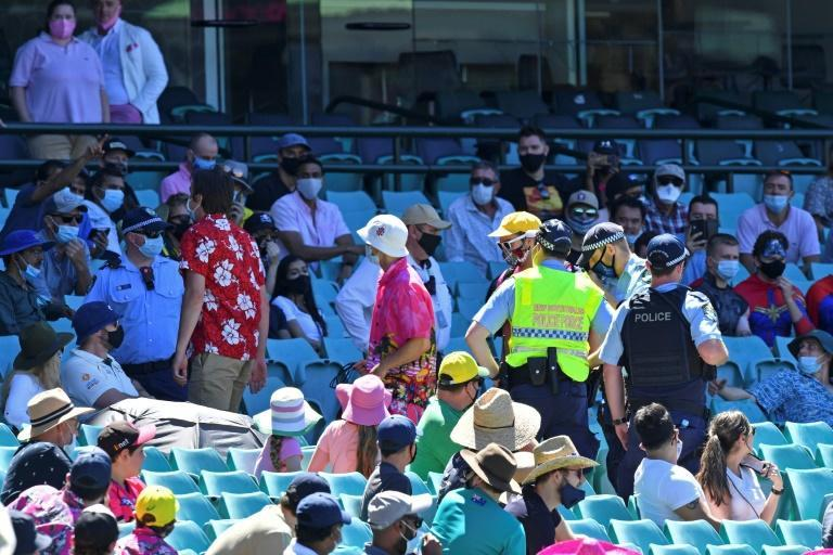 Police remove spectators from a section of the crowd after the third Test was halted just before tea on Sunday