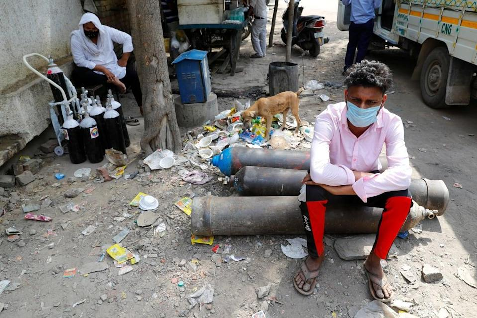 """<div class=""""inline-image__caption""""><p>Sumit Kumar, 28, sits on an oxygen cylinder as he waits outside a factory to get it refilled in New Delhi, India, April 28 2021.</p></div> <div class=""""inline-image__credit"""">REUTERS/Adnan Abidi/File Photo</div>"""