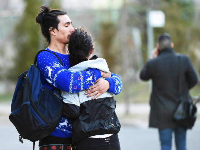 <p>Two people comfort each other after a rented van plowed down a crowded sidewalk, killing multiple people and injuring others before the driver fled and was quickly arrested in a confrontation with police, according to authorities, Monday, April 23, 2018, in Toronto. (Photo: Nathan Denette/The Canadian Press via AP) </p>
