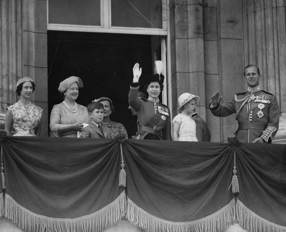 Princess Margaret, the Queen Mother, young Prince Charles and Princess Anne with their mother the Queen and father Prince Phillip wave from the balcony. (PA Images)