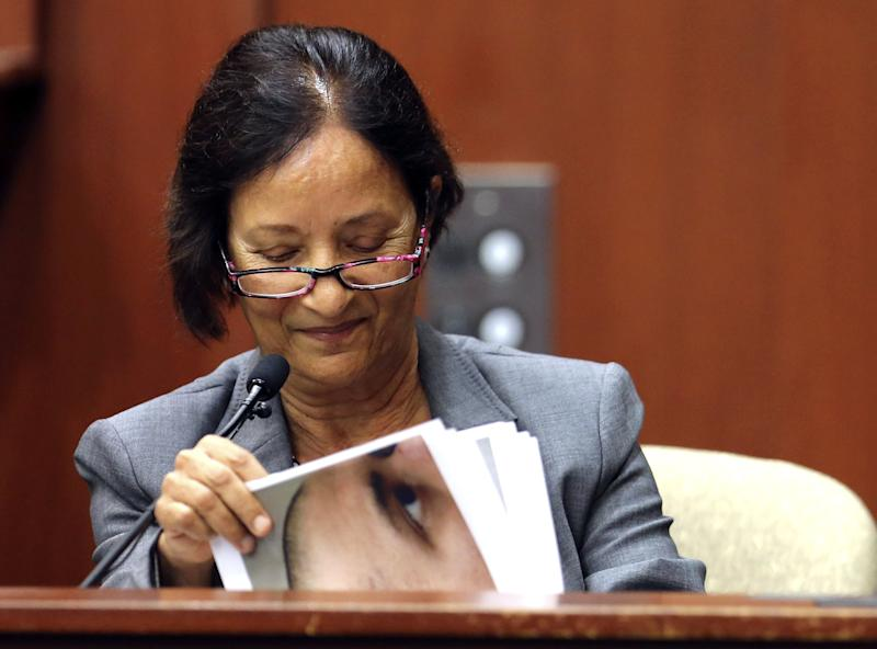 Jacksonville medical examiner Valerie Rao looks at photos as she testifies for the state in the trial of George Zimmerman in Seminole circuit court, in Sanford, Fla., Tuesday, July 2, 2013. Zimmerman is charged with second-degree murder in the shooting death of Trayvon Martin. (AP Photo/Orlando Sentinel, Joe Burbank, Pool)
