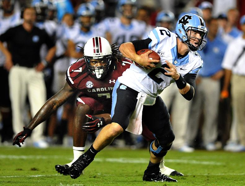 South Carolina defensive end Jadeveon Clowney (7) misses a sack of North Carolina quarterback Bryn Renner (2) during the second half of an NCAA college football game, Thursday, Aug. 29, 2013, in Columbia, S.C. A severe weather delay was called in the fourth quarter due to lighting in the area. South Carolina defeated North Carolina 27-10. (AP Photo/Stephen Morton)