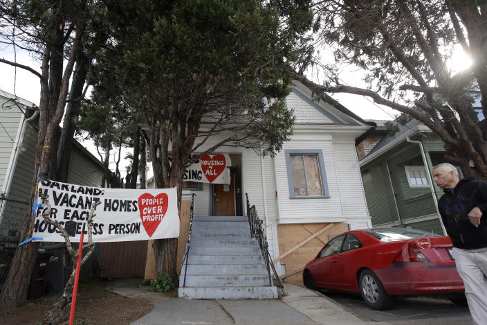 A man walks in front of a house that was occupied by homeless women in Oakland, Calif., Tuesday, Jan. 14, 2020. Homeless women ordered by a judge last week to leave a vacant house they occupied illegally in Oakland for two months have been evicted by sheriff's deputies. They removed two women and a male supporter Tuesday from the home before dawn in a case highlighting California's severe housing shortage and growing homeless population. (AP Photo/Jeff Chiu)