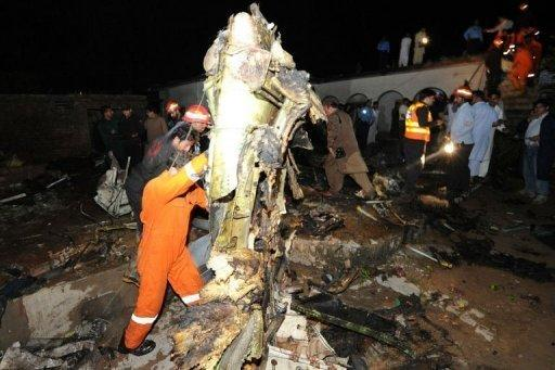 Pakistani rescue workers and local residents search the site of a plane crash in Rawalpindi