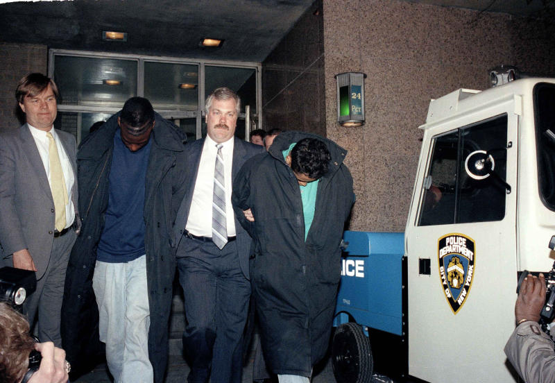 FILE - In this April 22, 1989 file photo, Yusef Salaam, 15, second from left, and Raymond Santana, 14, right, are led from the 24th Precinct by a detective after their arrest in connection with the rape and severe beating of a woman jogging in Central Park. Salaam, Santana and three other boys maintained their innocence as they grew up behind bars after being convicted of the attack. Their convictions were eventually tossed out by a judge in 2002 when new evidence surfaced linking someone else to the crime. But their legal battle goes on: A $250 million federal lawsuit against police and prosecutors has been pending nearly a decade, with no resolution in sight. (AP Photo/David Burns, File)