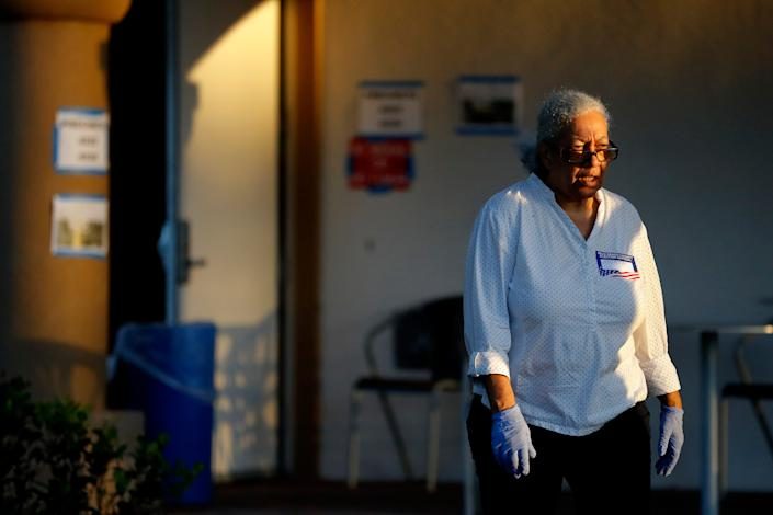 A polling place worker uses gloves outside of the Boca Raton Library during the Florida primary election, Tuesday, March 17, 2020, in Boca Raton, Fla. As Florida officials try to contain the spread of the novel coronavirus, the state's voters headed to the polls to cast ballots in the Democratic presidential primary.