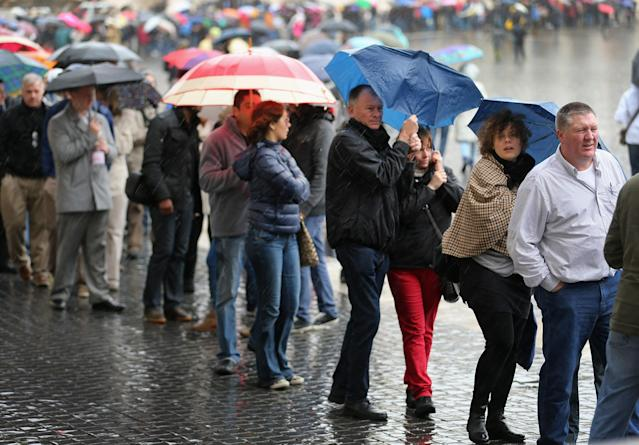 VATICAN CITY, VATICAN - MARCH 18: People stand in a line in pouring rain as they wait to visit Saint Peter Basilica the day before the inauguration mass on March 18, 2013 in Vatican City, Vatican. The Inauguration Mass for Pope Francis will take place on March 19, the feast day for St. Joseph. (Photo by Joe Raedle/Getty Images)