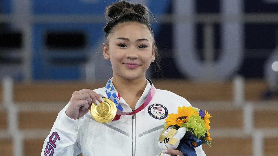 Gold medalist Sunisa Lee of the United States displays her medal for the artistic gymnastics women's all-around at the 2020 Summer Olympics, Thursday, July 29, 2021, in Tokyo. (AP Photo/Gregory Bull)