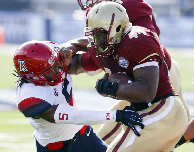 Boston College running back Andre Williams (44) pushes away Arizona cornerback Shaquille Richardson (5) on a short run during the first half of the AdvoCare V100 Bowl NCAA college football game, Tuesday, Dec. 31, 2013, at Independence Stadium in Shreveport, La. (AP Photo/Rogelio V. Solis)