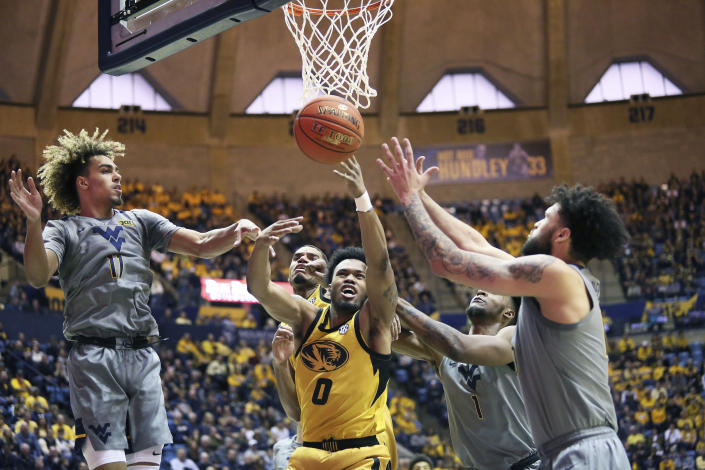 Missouri guard Torrence Watson (0) goes to make a shot as he is defended by West Virginia forwards Emmitt Matthews Jr. (11) and Derek Culver (1), and guard Jermaine Haley (10), during the first half of an NCAA college basketball game Saturday, Jan. 25, 2020, in Morgantown, W.Va. (AP Photo/Kathleen Batten)