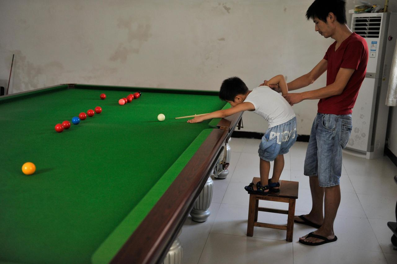 Three-year-old Wang Wuka plays a shot as his father Wang Yin steadies his arm during snooker practice at their home in Xuancheng, Anhui province, September 14, 2013. Wang Yin, a snooker fan, has been teaching his son the sport for more than two years. The boy, who vows to be a top snooker player, undergoes five hours of training daily to shoot the balls with precision. Picture taken September 14, 2013. REUTERS/Stringer (CHINA - Tags: SPORT SOCIETY) CHINA OUT. NO COMMERCIAL OR EDITORIAL SALES IN CHINA