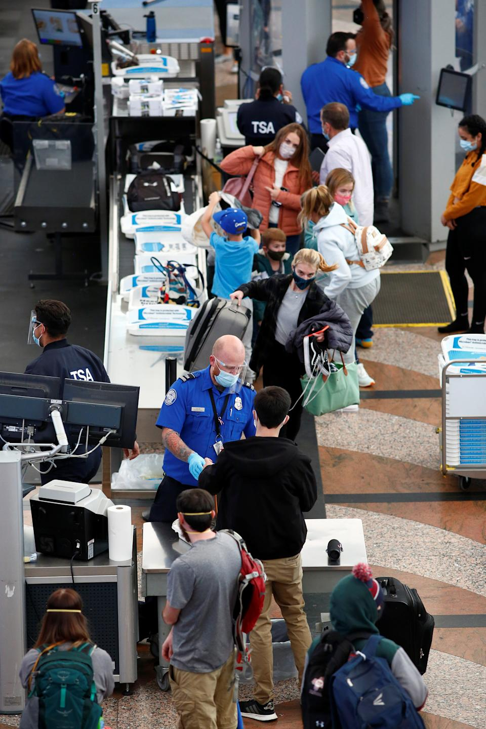 Travelers wearing protective face masks to prevent the spread of the coronavirus disease (COVID-19) go through security before boarding a flight at the airport in Denver, Colorado, U.S., November 24, 2020.