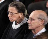 FILE - In this Jan. 24, 2012, file photo Supreme Court Justices Ruth Bader Ginsburg and Stephen Breyer listen to President Barack Obama deliver his State of the Union address to a joint session of Congress at the Capitol in Washington. Ginsburg didn't put on her judge's robe without also fastening something around her neck. Ginsburg called her neckwear collars, or jabots, and they became part of her signature style, along with her glasses, lace gloves and fabric hair ties known as scrunchies. (AP Photo/Evan Vucci, File)