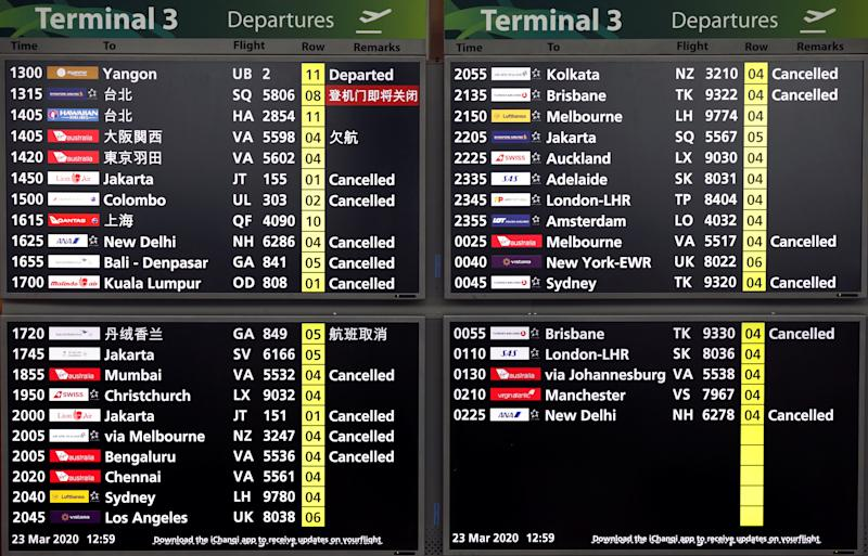 A flight information board shows cancelled flights, as airlines reduce flights following the outbreak of the coronavirus disease (COVID-19), at Singapore's Changi Airport March 23, 2020. REUTERS/Edgar Su