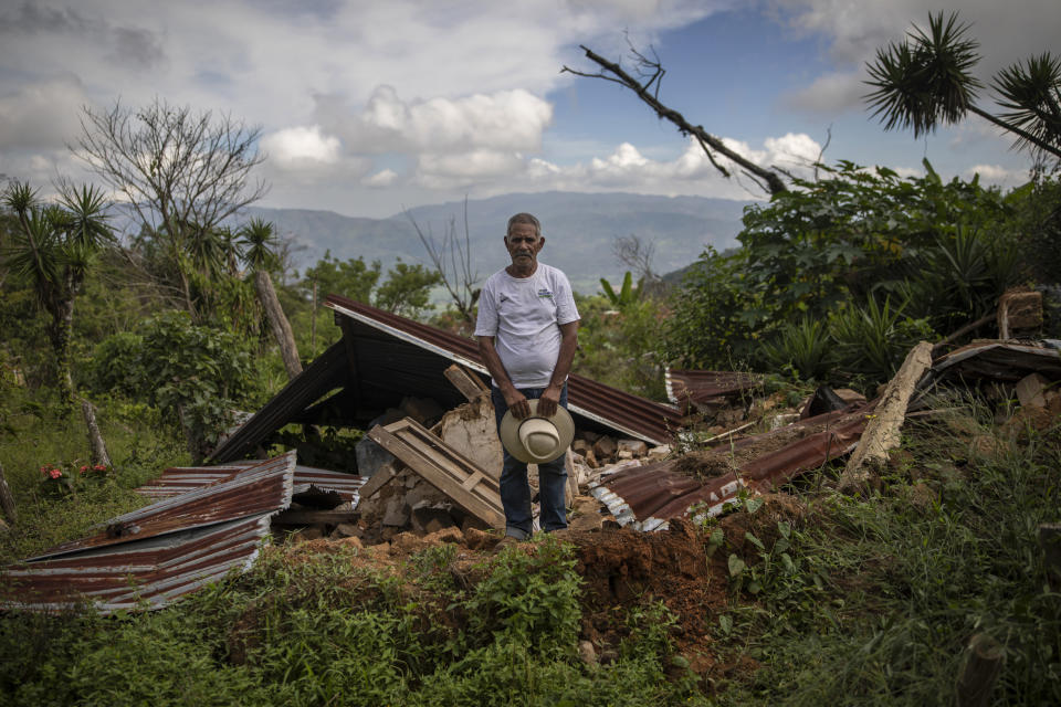 """Julio Villanueva Melgar, 70, stands for a portrait among the remains of his home destroyed by a landslide triggered by hurricanes Eta and Iota in the village of La Reina, Honduras, Wednesday, June 23, 2021. Over the decades, he raised a family and made a living in La Reina. But now he feels as if he's been hurled into a new and more hostile universe. """"One becomes crazy, disoriented. ... You don't fit in anymore."""" (AP Photo/Rodrigo Abd)"""