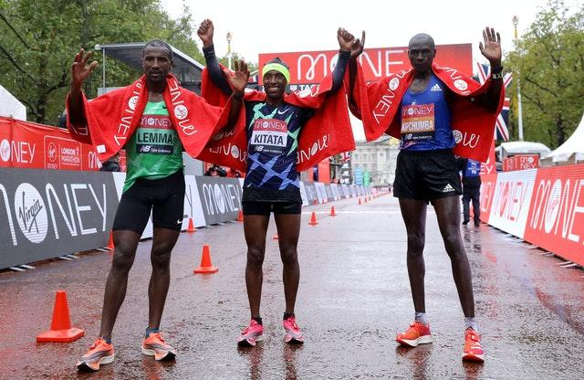 Ethiopia's Shura Kitata (centre) celebrates victory alongside second-placed Vincent Kipchumba of Kenya (right) and third-placed Sisay Lemma of Ethiopia