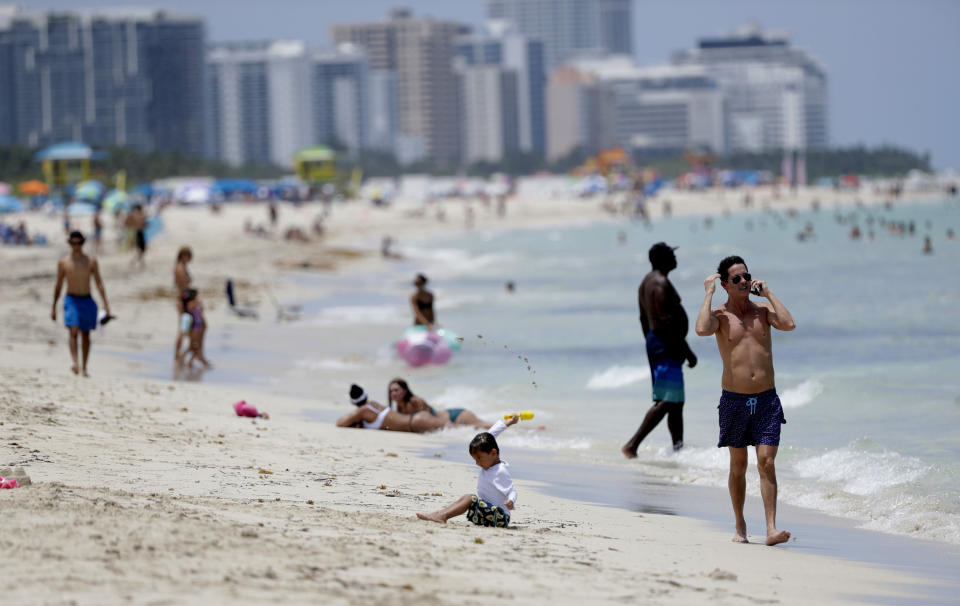 Beach goers walk along the shore on Miami Beach, Florida's famed South Beach, Tuesday, July 7, 2020. Beaches in Miami-Dade County reopened Tuesday after being closed July 3 through 6 to prevent the spread of the new coronavirus. (AP Photo/Wilfredo Lee)