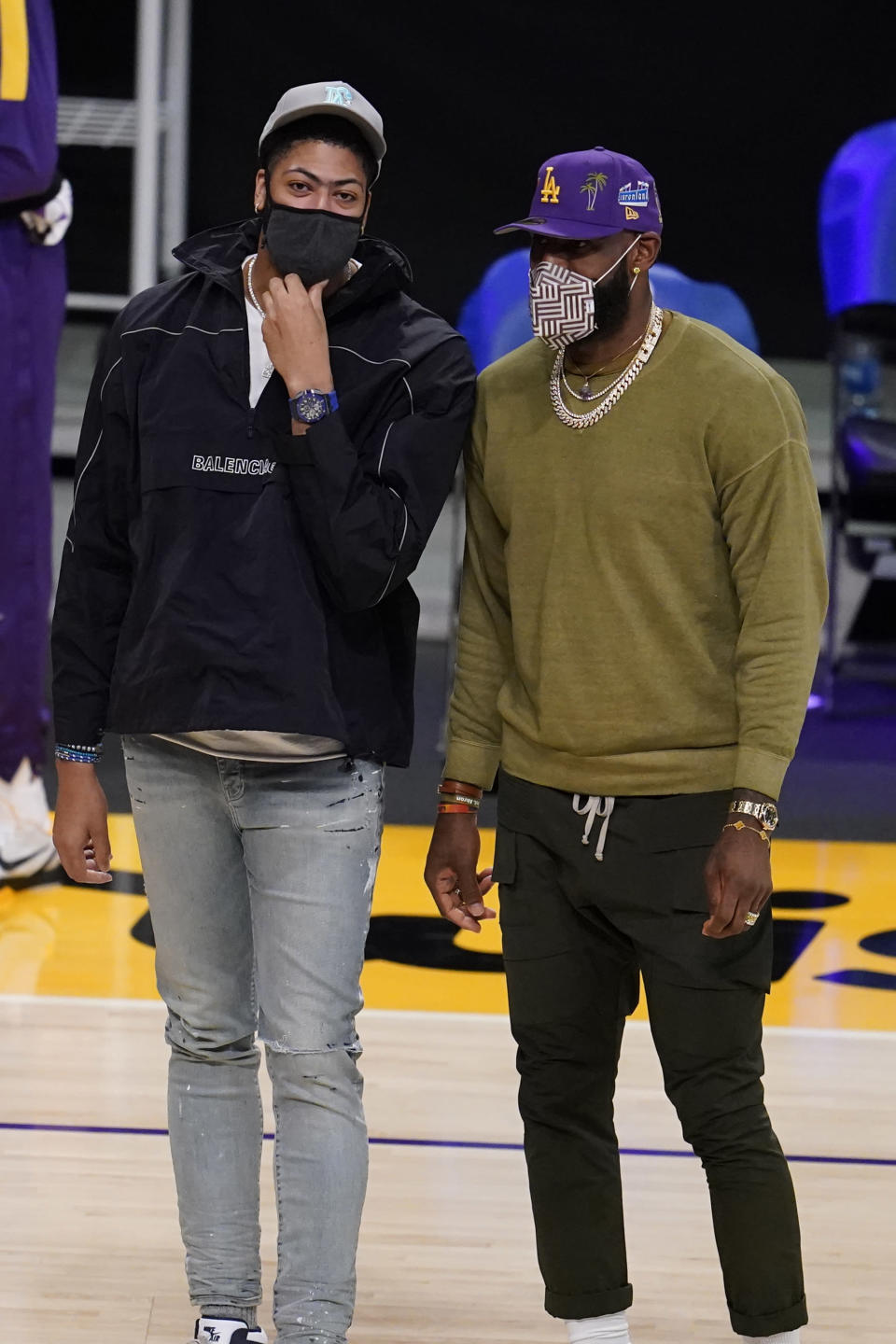 Los Angeles Lakers injured players Anthony Davis, left, and LeBron James talk on the court during a timeout during the first half of an NBA basketball game against the Utah Jazz Monday, April 19, 2021, in Los Angeles. (AP Photo/Marcio Jose Sanchez)