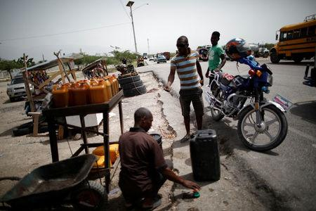 A man buys gasoline at a stand displaying fuel for sale on the outskirts of Port-au-Prince, Haiti, July 12, 2018. REUTERS/Andres Martinez Casares