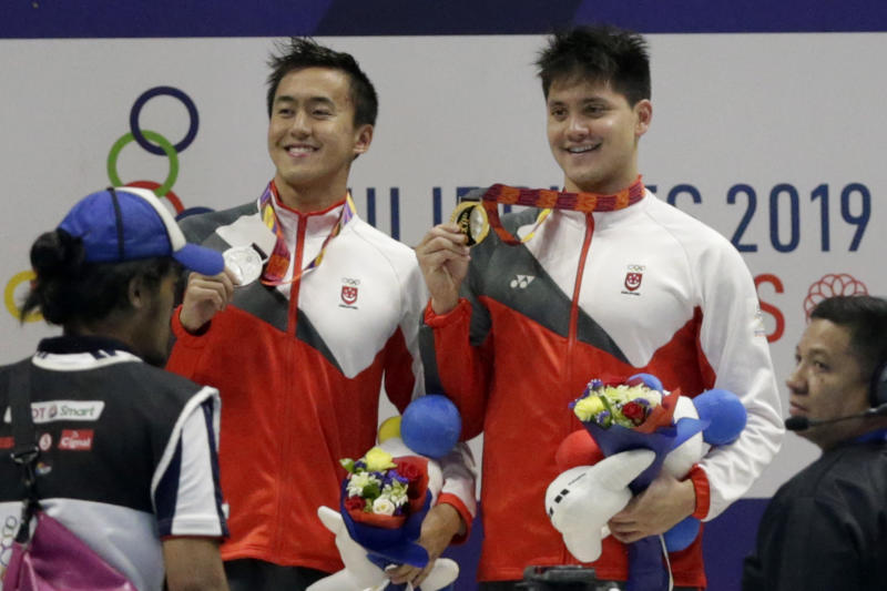 Gold medalist Singapore's Joseph Schooling,right, poses with silver medalist Singapore's Zheng Wen Quah during awarding ceremonies for the men's 100m butterfly final during swimming competition at the 30th Southeast Asian Games in New Clark City, Tarlac province, northern Philippines on Friday, Dec. 6, 2019. (AP Photo/Tatan Syuflana)