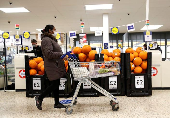 A woman wearing a face mask pushes a shopping cart at a Tesco supermarket in Hatfield, Britain October 6, 2020. REUTERS/Peter Cziborra/File Photo