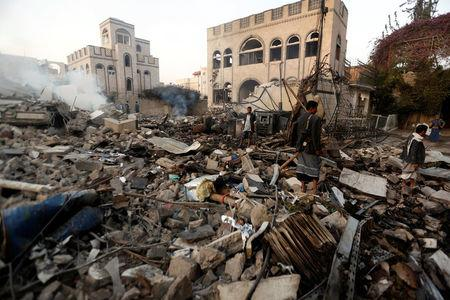 Guards walk on the wreckage of a building destroyed by air strikes in Sanaa, Yemen