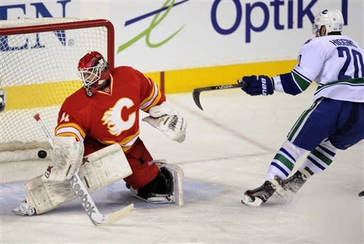 Vancouver Canucks' Chris Higgins, right, scores on Calgary Flames' goalie Daniel Taylor during first period NHL action in Calgary on Sunday, March 3, 2013. (AP Photo/The Canadian Press, Larry MacDougal)