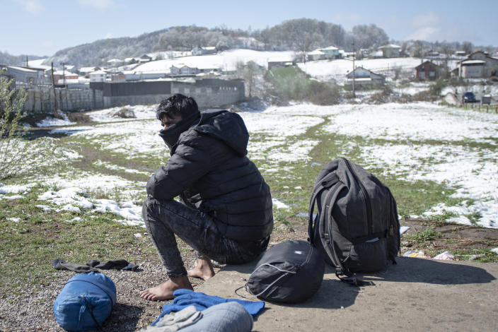 A migrant man dries his belongings outside the Miral camp, in Velika Kladusa, Bosnia, Wednesday, April 7, 2021. Bosnia is seeing a rise in coronavirus infections among migrants and refugees living in its camps, as it struggles to cope with one of the Balkans' highest COVID-19 death and infection rates among the general population.(AP Photo/Davor Midzic)