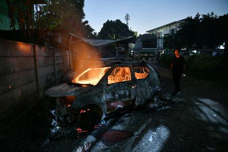 A man looks at a car that was set on fire by protesters at Brimob (Mobile Police) Dormitory Complex, Petamburan, Jakarta, Indonesia, May 22, 2019 in this photo taken by Antara Foto. Antara Foto/Sigid Kurniawan/ via REUTERS