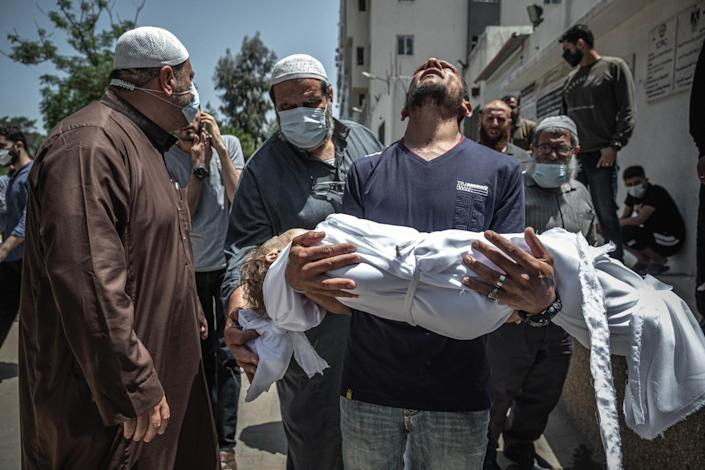 A man holds his dead child.