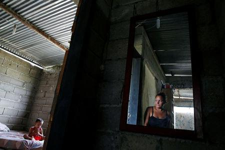 Oleydy Canizalez (R), 29, looks at her son Luis, 3, while he eats lunch, before her sterilization surgery, at their home in Charallave, Venezuela July 7, 2016. REUTERS/Carlos Garcia Rawlins