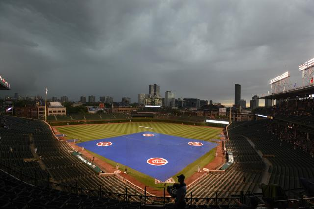 The tarp covers the infield as rain delays the start of a baseball game between the Chicago Cubs and Pittsburgh Pirates at Wrigley field in Chicago, Saturday, June 21, 2014. (AP Photo/Paul Beaty)