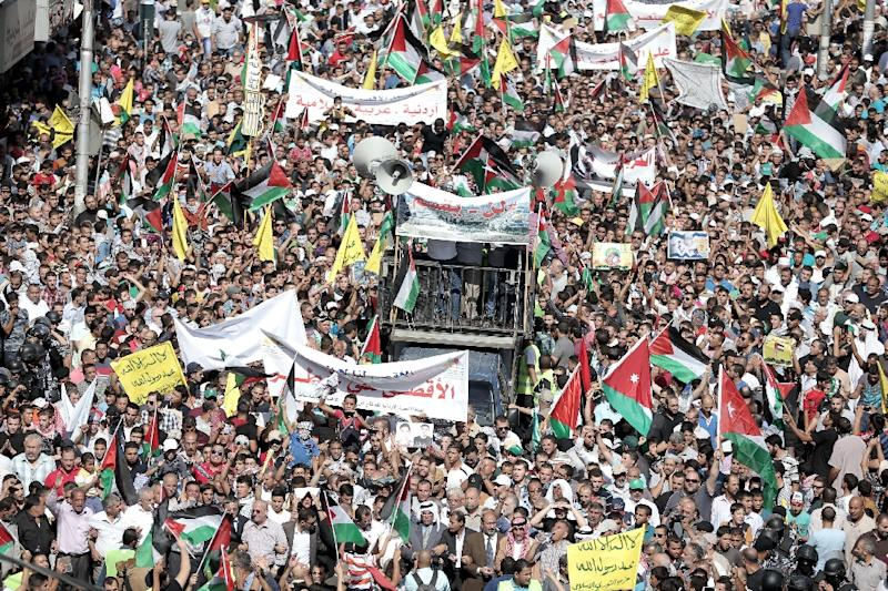 Jordanian protesters wave the national and Palestinian flags during a demonstration near the Israeli Embassy in the capital Amman in solidarity with the Palestinians on October 16, 2015