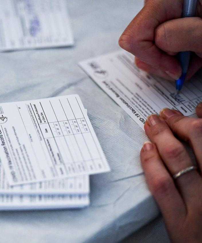 Blandon, PA – April 14: A healthcare worker fills out information on COVID-19 Vaccination Record Cards from the CDC. At the Giorgio Companies site in Blandon, PA where the CATE Mobile Vaccination Unit was onsite to administer Moderna COVID-19 Vaccines to workers Wednesday morning April 14, 2021. The effort was a collaboration between the Latino Connection, the Pennsylvania Department of Health, Highmark Blue Shield, and the Independence Blue Cross Foundation. (Photo by Ben Hasty/MediaNews Group/Reading Eagle via Getty Images)