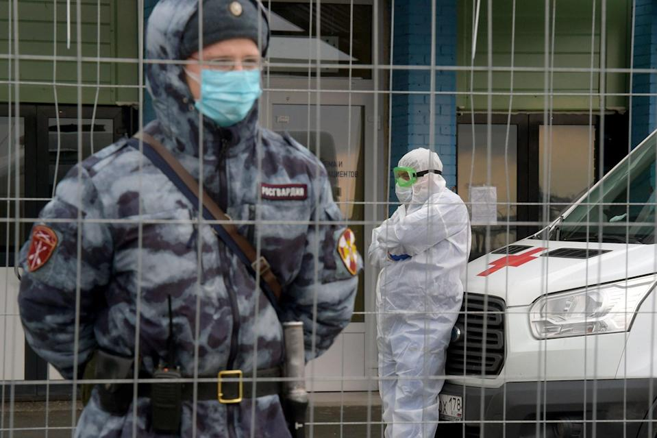 Russian National Guard and doctor stand outside Covid hospital in St Petersburg (AFP via Getty Images)