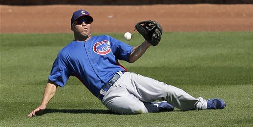Chicago Cubs right fielder Scott Hairston tries to get control of a single hit by Texas Rangers' Mitch Moreland during the fourth inning of an exhibition spring training baseball game on Wednesday, March 6, 2013, in Surprise, Ariz. (AP Photo/Charlie Riedel)